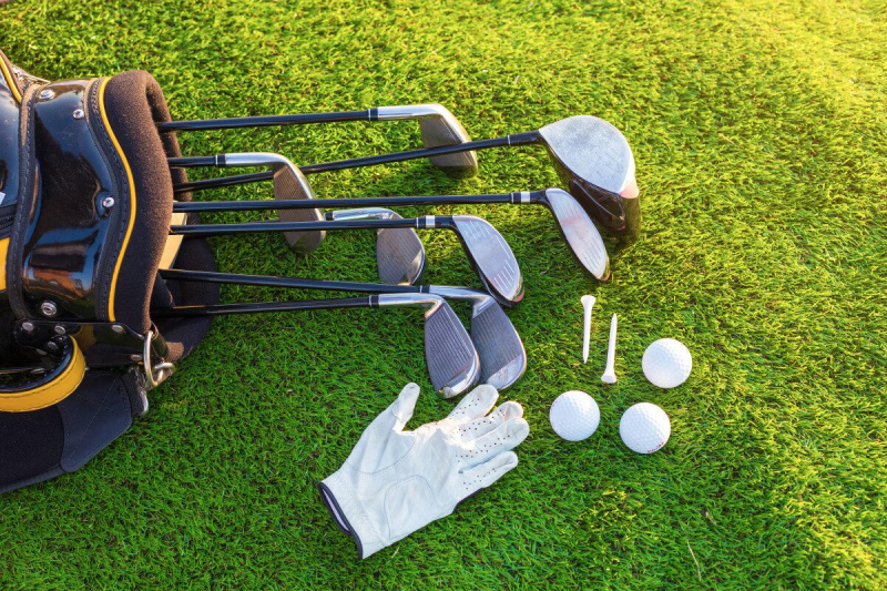 Image of Golf Clubs, Balls and Cloves In Grass.