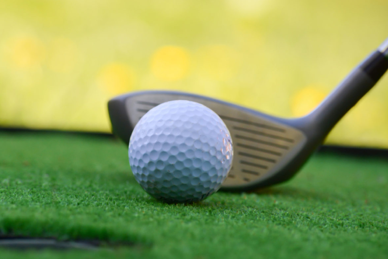 A Close-up view of Golf club and ball in grass.