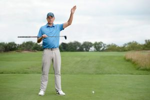 Image of a professional golfer with golf club and ball.