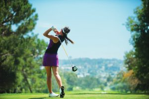 Female Golfer taking a shot in the golf course.