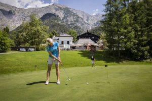 Female Golfer taking a shot in a golf ground.